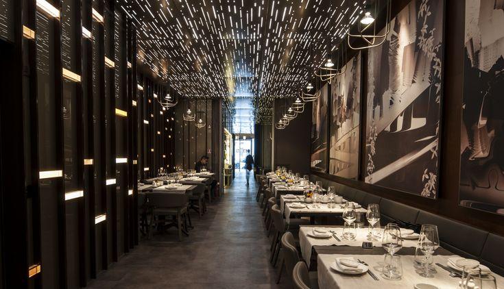 Una parete è costituita da una boiserie in vetro retro-verniciato dai motivi geometrici interrotti da piccoli volumi luminosi in policarbonato colorato