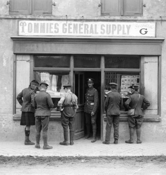 """WWI, 6 August 1917; Shop in the village of Ghyvelde near Dunkerque. Note the sign """"Tommies General Supply"""", Branch G. Cropped. © IWM (Q 2683)"""
