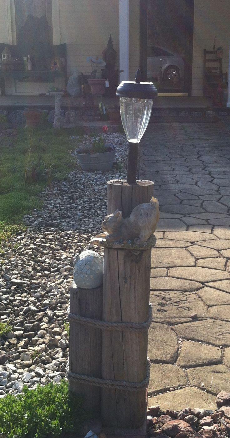Add small statues to solar light holder made from landscape timbers