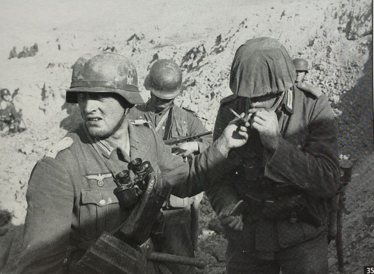 The unknown Leutnant lights his cigarette from the pipe of an Oberleutnant from Inf. Reg.577. In an effort to avoid standing out to enemy snipers, both officers carry the standard Kar98K rifle instead of MP-40s and the Lieutenant has toned down the whiteness of his officer's shoulder straps. Inf.Rgt. 577 lost only one officer on 14 Oct: Lt. Werner Schwederer, a platoon commander from 7. Kcompanie, was killed.