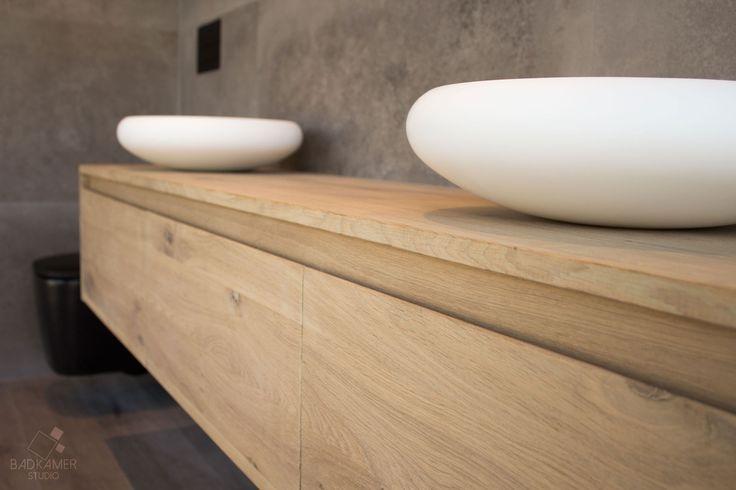 Robuuste maatwerk badkamer. Deze badkamer voelt warm aan door de houten vloer en het eikenhouten wasmeubel. Toch is hij ook stoer door de vierkante beton-look tegels. Het vrijstaande Solid Surface bad met aparte vorm, staande mat-zwarte kraan en spiegel met LED-verlichting mogen niet ontbreken. Het mat-zwarte toilet maakt het geheel af #badkamerstudio #badkamerstudiobreda #badkamerstudioutrecht