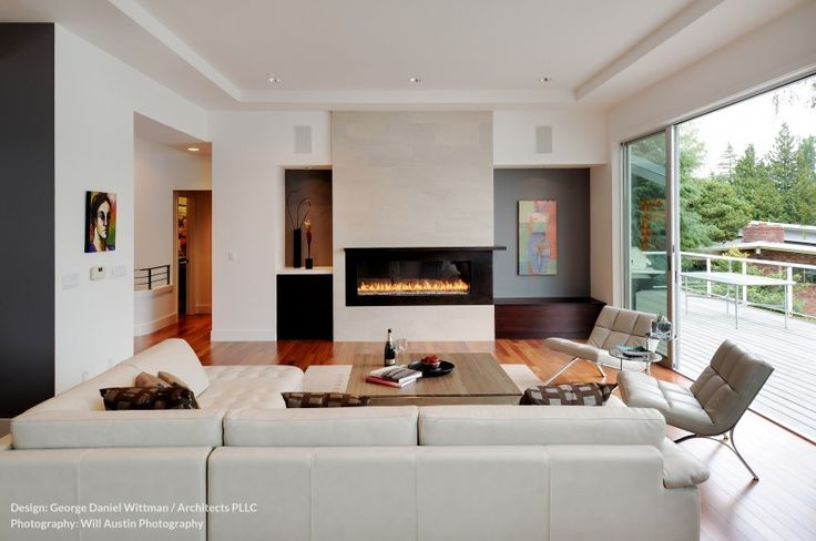 A spacious, contemporary living room with a fireplace that can be enjoyed from two sides and low-profile furniture in a light beige. Glass pocket doors can be retracted to reach the back deck.