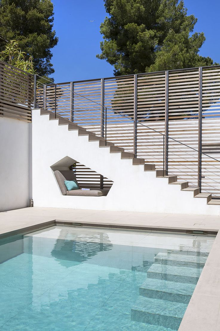 This built-in seating nook is tucked under the stairs by this swimming pool at a house in Saint Tropez.