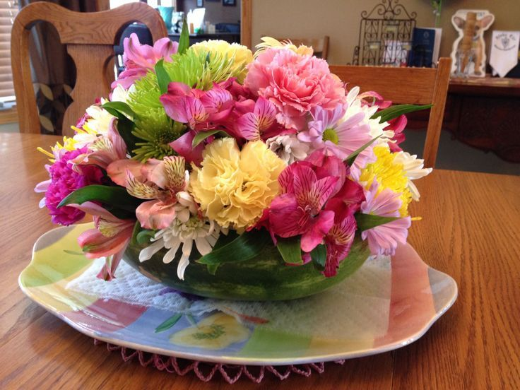 Flower arrangement in a watermelon! Hollow out half a watermelon, fill it with gravel, mix a pitcher of water with flower food packet & pour over the gravel, then arrange your flowers - VOILA!! A perfect DIY summertime centerpiece! :)
