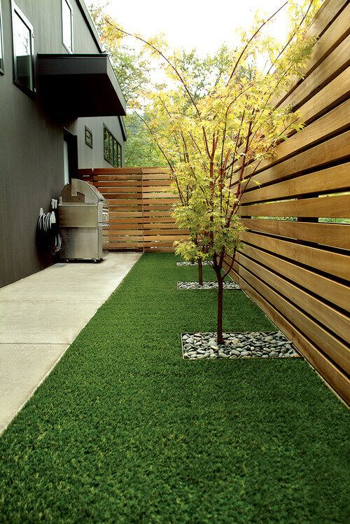 The small space between this fence has a nice piece of astroturf. This is a perfect use of astroturf. Lawn care can be particularly tricky along fences and walls, but there is no need for concern when you are dealing with astroturf.