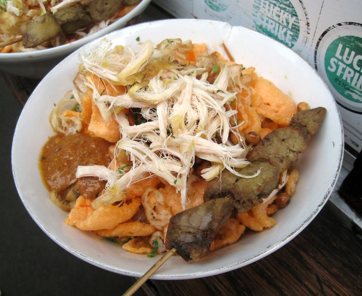 A Bubur Ayam (chicken rice congee) with chicken liver satay, sold by travelling vendor cart that frequenting kampung or residential area every morning in Jakarta, Indonesia.
