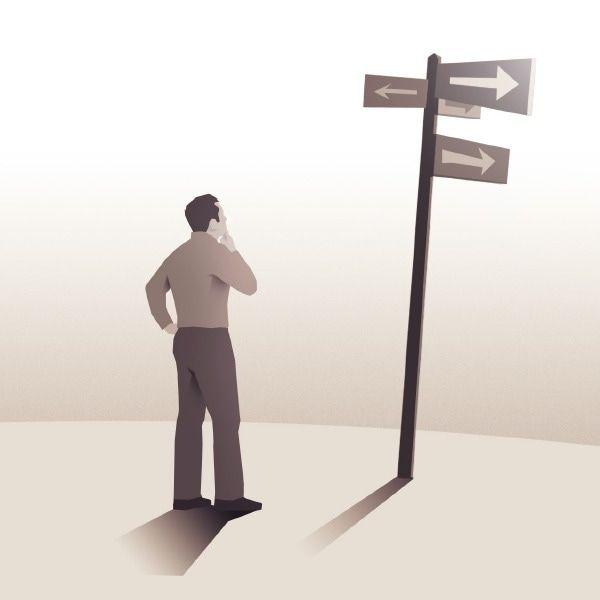 A man contemplates signs at a crossroad