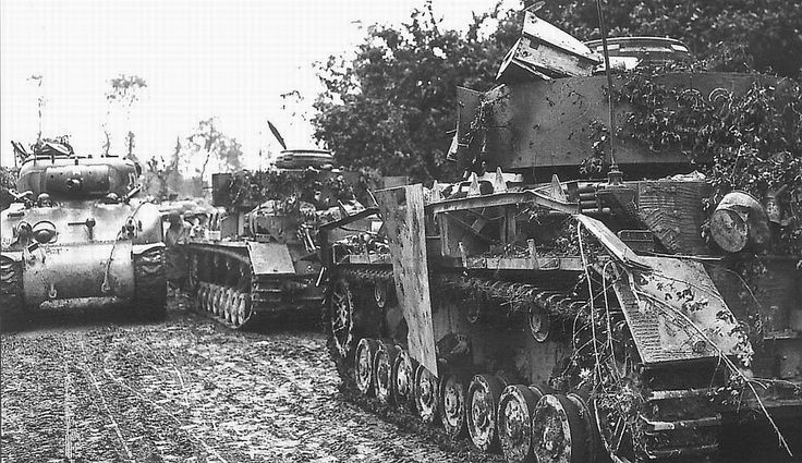 An American M4 Sherman confidently passes a knocked out armored column of German…
