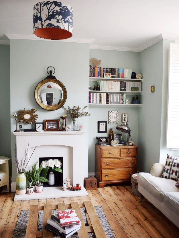 We take a tour of design blogger Ruth Mathew's beautiful modern eclectic Scandinavian bohemian glam home. This living room is beautifully styled with pale blue walls, colourful accessories, a round mirror above the fireplace and stripped wooden floor.