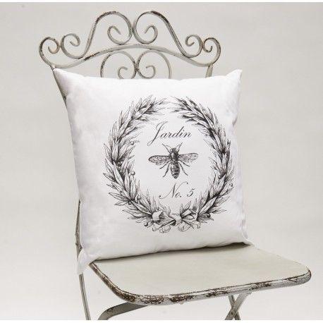 Biała ozdobna poduszka Jardin marki French Home ,z motywem pszczoły w laurowym okręgu, będzie doskonałym dodatkiem do każdego salonu.