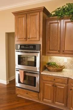 Staining and glazing your kitchen cabinets revitalizes the look of your kitchen.
