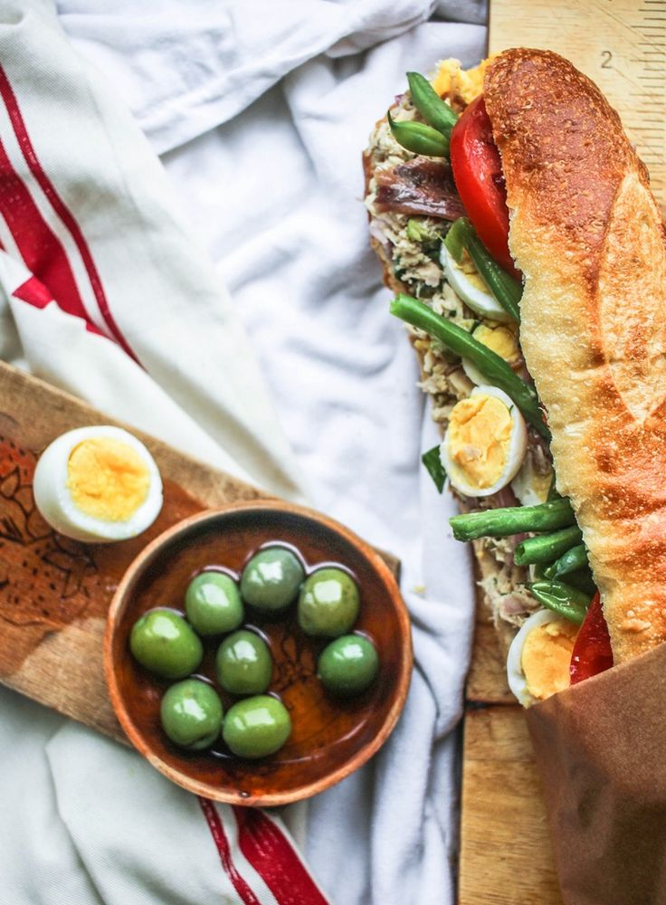 Planning a picnic party for a crowd or just couples (like you and your date)? You're surely in need of more food ideas! This classy sandwich, a classic of southern France, is perfect picnic fare. It's a Niçoise salad in a sandwich that wants — nay, needs — to be made in advance, so the bread soaks up the delicious flavors.