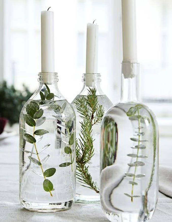Stellen Sie sich Kerzenständer über Flaschen vor, die mit Wasser und Pflanzen gefüllt sind.