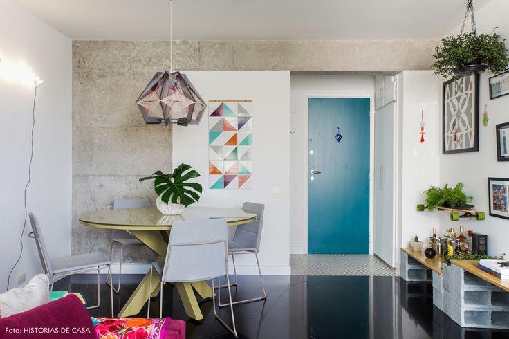 Sala de jantar tem estrutura de concreto aparente, porta pintada de azul e aparador feito com blocos de concreto e OSB.
