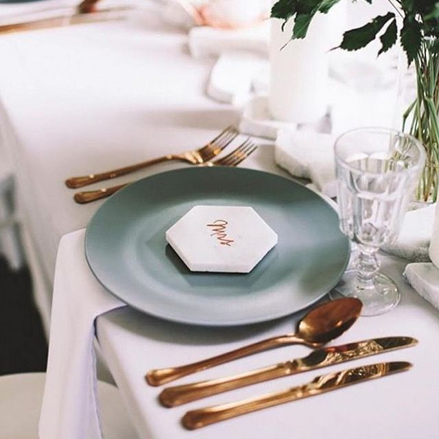 White table cloths, copper cutlery, teal charger plates, marble place cards and crystal glassware