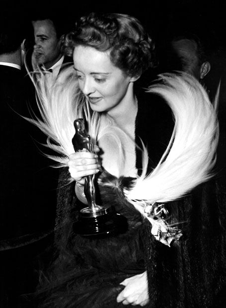 1939: Bette Davis attends the Academy Awards dinner clutching her Best Actress award for Jezebel  Picture: Everett Collection / Rex Features