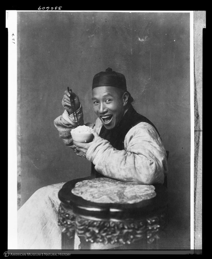 Be like this guy: A picture from 1904 — yes, 1904 — of a man smiling while eating rice. (Laufer/AMNH)