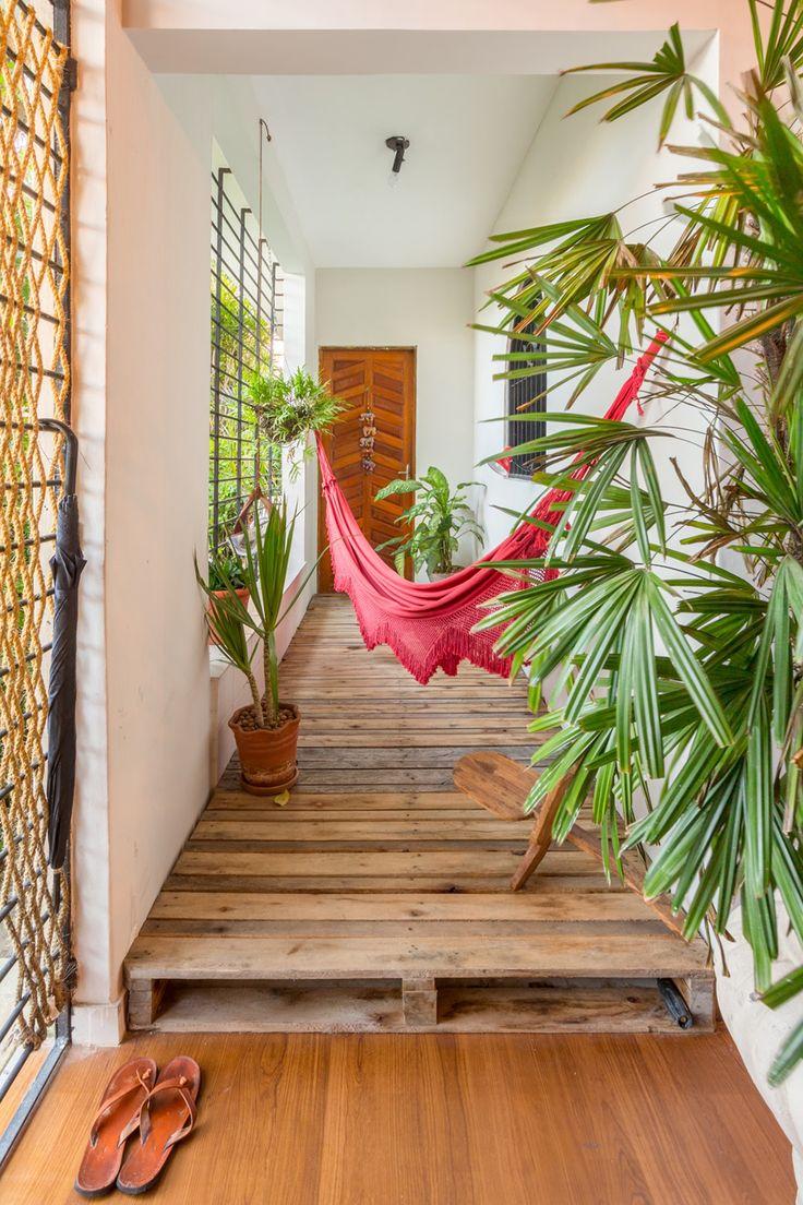 Inspiração de pallets na decoração: já pensou usá-los para realçar o corredor? Nesse ambiente com plantas e rede, o resultado ficou super aconchegante.