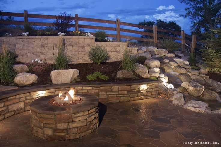 A contemporary style patio with a raised garden bed, stone retaining wall and stone fire pit surround. See 7 ways to make your patio even more awesome.