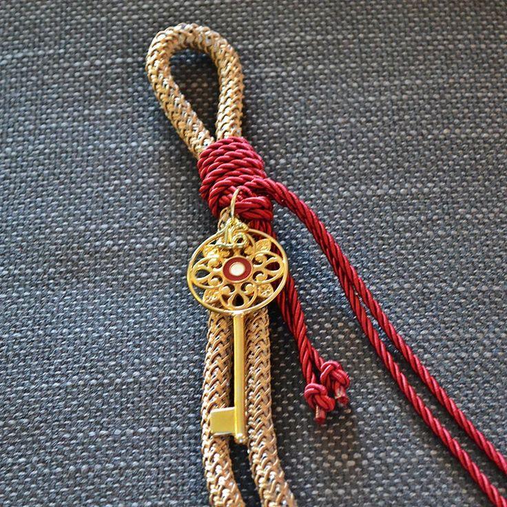 Για να ξεκλειδώσετε την τύχη σας ή την καρδιά όποιου αγαπάτε, αυτό το κλειδί είναι το κατάλληλο. Δεμένο με καφέ και κόκκινο κορδόνι , με σχέδια στο κέντρο του κλειδιού και με σμάλτο λευκό και κόκκινο.