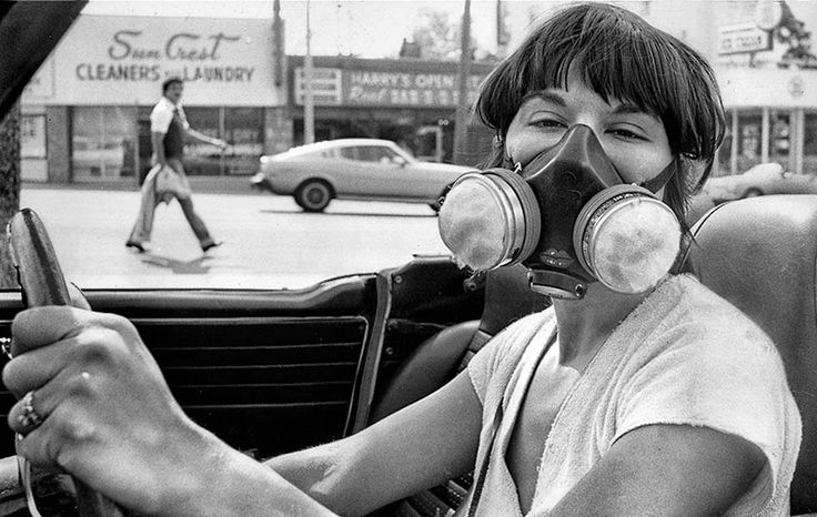 A woman donning a gas mask during a Los Angeles smog alert, June 1979