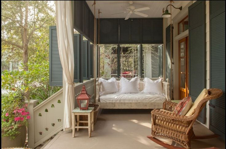 Porch with daybed, lots of cushy pillows, wicker chair, shutters.  Beautiful.