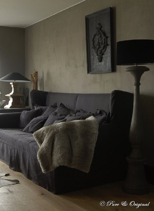 Gray and black living room with gray textured walls, slipcovered black wingback sofa with black pillows, faux fur throw and gray washed wood floor lamp with black lamp shades.
