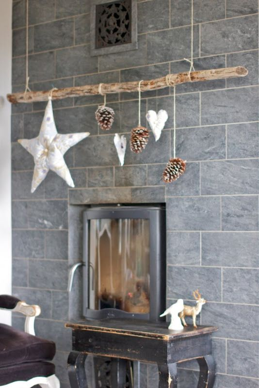 pine cone and star mobile from picture rail over fireplace