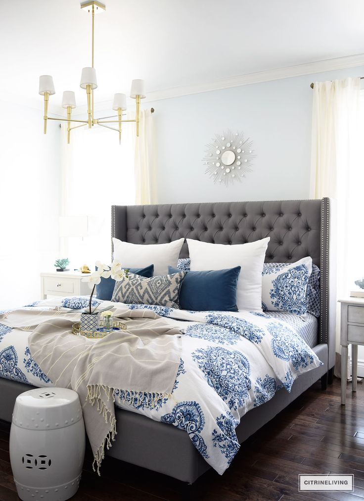 Gorgeous blue and white bedroom featuring blue and white bedding paired with global inspired textiles, grey upholstered bed and brass accents and lighting bring a bright and airy look to any bedroom.