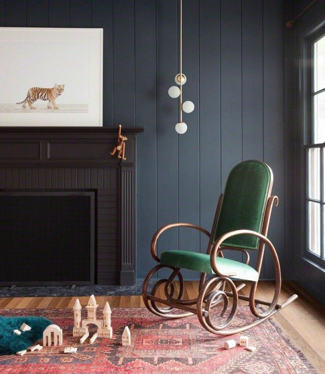 Modern nursery with navy blue walls, a black fireplace, a Persian rug, and a vintage rocker