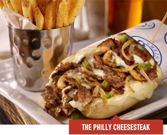 The Philly Cheesesteak - Thin slices of steak on a warm hoagie roll (both imported from South Philly). Topped with cheese. Served with seasoned french fries. Available with grilled onions, mushrooms or green bell peppers.