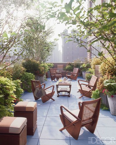 Midcentury teak-and-cane furniture with cushions covered in Perennials fabrics fill the spacious terrace of this duplex apartment.