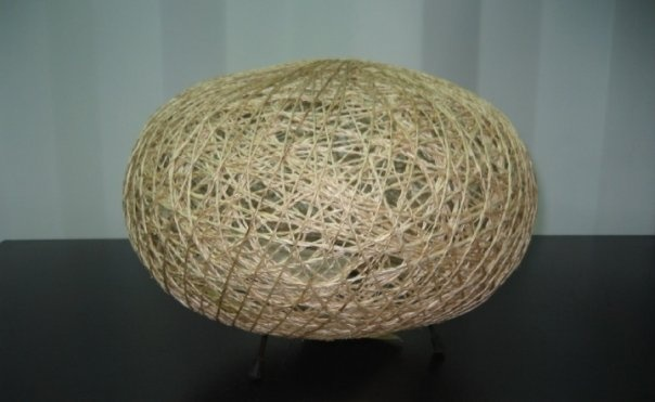 This Oval Table Lamp is made from twined hemp that is wrapped in layers.  This layering casts an interesting shadow pattern into the room it sits in.  Comes with a metal wire base with rubber feet for scratch free standing on a table.