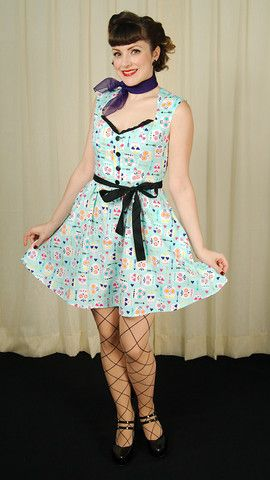 This Dia de los Muertos sugar skull dress is just so sweet! The dress has a turquoise background with white sugar skulls and hearts and arrows, all in purple, orange, red, gold, yellow, etc. The 100% cotton A-line dress has a ruffled swe...