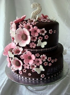 pink flowers and tiny white butterflies on this chocolate cake