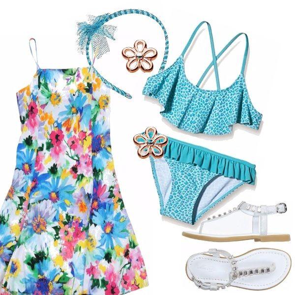 Grazioso abito con spalline in una allegra fantasia floreale. Bikini azzurro con disegni bianchi. Sandalo bianco infradito con pietre. Cerchietto per capelli azzurro, orecchini dorati a forma di fiore.
