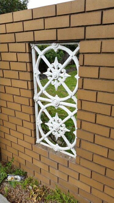 White metal detail in brick fence