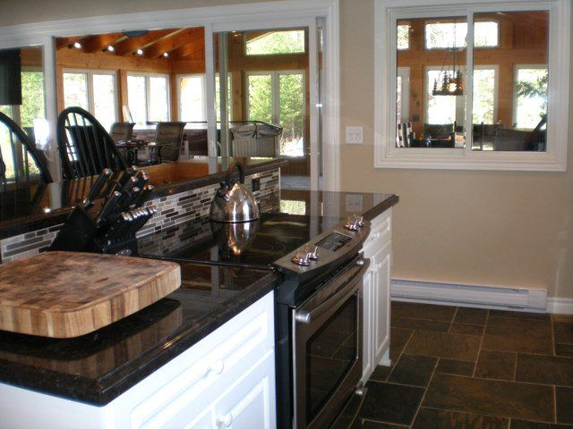 Kitchen island with stove top, oven, and bar on the other side ...