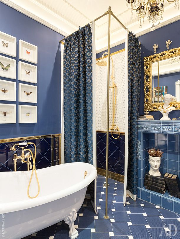 Bathroom solved in white, blue and gold tones. The chandelier remained in the apartment from the old interior.