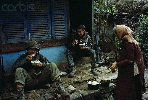 13 Feb 1968, Hue, South Vietnam --- U.S Marines eat a bowl of rice which was served to them by a South Vietnamese woman. --- Image by © Bettmann/CORBIS