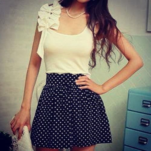 Camiseta blanca con lazos y falda azul con puntos blancos. <3