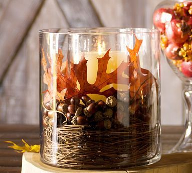 large glass hurricane filled with grapevine, pine nuts, leaves and candle