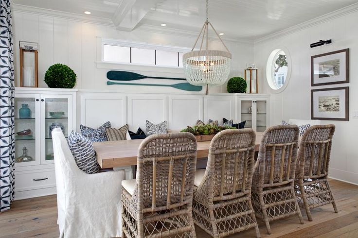 This lovely white beach home features coastal decor throughout. The living room includes a fireplace surrounded by built-in shelves. One of the bedrooms has a headboard made from an assortment of oars. A roof deck with wicker furniture and a glass-enclosed fire pit provides a great view of the nearby ocean.