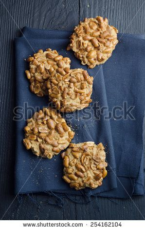 Homemade cookies with peanuts over black wooden table, above view
