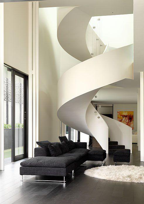 Spiral staircase, dark gray couch, dark wood floors.