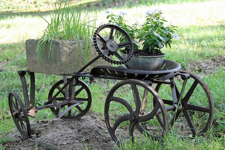 Use over sized tractor seat, smaller set of wheels on axle and medium sized wagon wheels back. Gear for steering wheel if cant find old one from tractor. Don't like cement on front, maybe old trough or feeder.