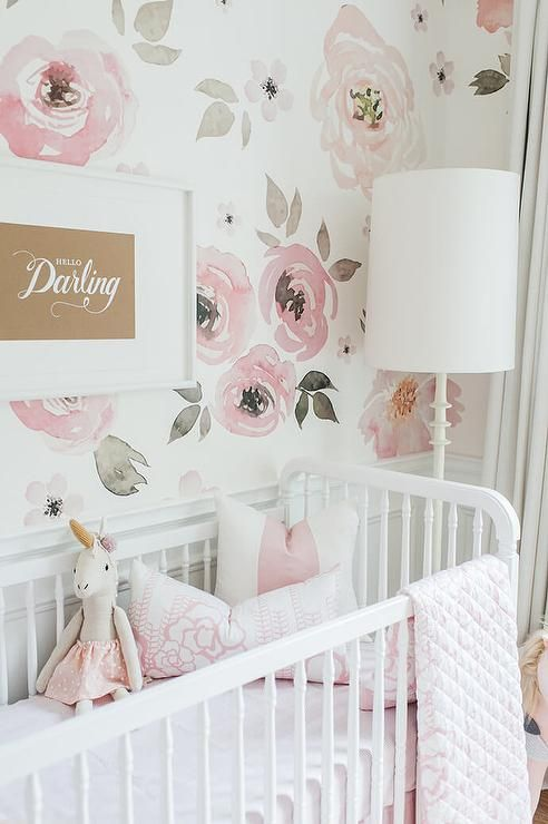 Whimsical pink girl's nursery boasts a Jenny Lind Floor Lamp sat beside a white Franklin and Ben Crib dressed in Olio Crib Bedding and positioned against wainscoted lower walls accented with lower walls covered in Jolie Wallpaper holding a Perfectly Smitten Hello Darling Print.