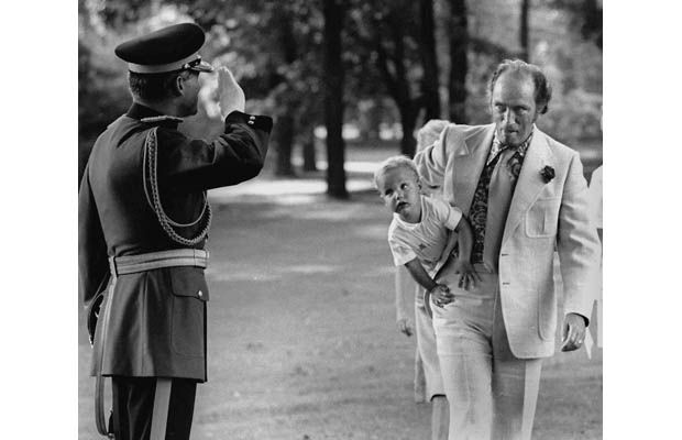 Prime Minister Pierre Trudeau arrives at a Garden Party at Government House , August 1973, with Justin under his arm, as an RCMP salutes.