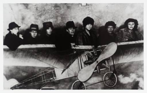 Photograph of Bloomsbury artists in a fake plane. They are (from left to right): Unknown, David Garnett, Vanessa Bell, Oliver Strachey, Dora Carrington, Duncan Grant, and Barbara Bagenal.