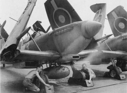 A Royal Navy Fleet Air Arm Seafire fighter being warmed up on board the aircraft carrier HMS Implacable while ratings hold chocks under the wheels. The 89 gallon ex P-40 Warhawk drop tank is prominent. Seafire Mk III